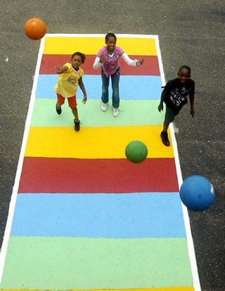 Students playing shuffle board at recess with new playground equipment and court.